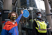 Blue plaque which talks of links to slavery and fossil fuel projects is pasted up outside the Lloyd's of London building on the Walk of Shame disruptive mach through the City of London by environmental group Extinction Rebellion on 4th September 2020 in London, United Kingdom. The walk visited various locations in the financial district, to protest against companies and institutions with historical links to the slave trade, or who finance or insure projects which are seen as ecologically unsound. The message by the group is that 'apologies and token attempts at diversity are not enough to address this legacy and present reality. Our demand is reparations and reparatory justice for those affected by colonial and neo-colonial exploitation'. Extinction Rebellion is a climate change group started in 2018 and has gained a huge following of people committed to peaceful protests. These protests are highlighting that the government is not doing enough to avoid catastrophic climate change and to demand the government take radical action to save the planet.