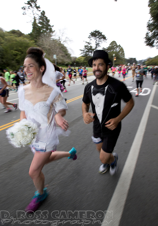 Bride Jackie Mayer, left, and groom Brent Blum run through Golden Gate Park during the 104th running of the Bay to Breakers 12k, Sunday, May 17, 2015 in San Francisco. Tens of thousands of runners, some clad in costume and some in nothing at all, populated the 7.42-mile route. (D. Ross Cameron/Bay Area News Group)