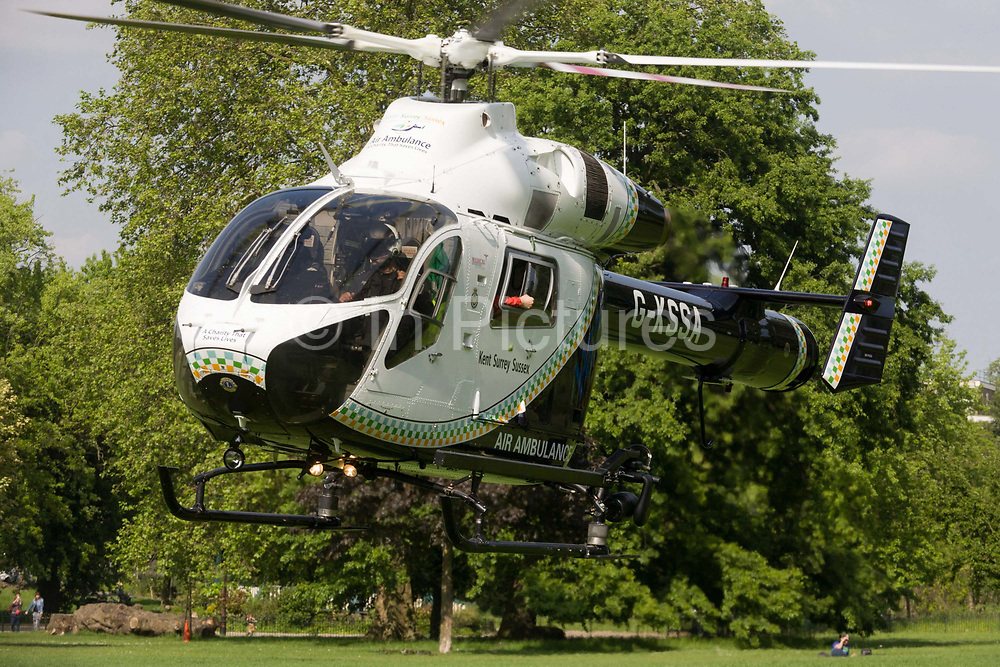 MD902 Explorer helicopter from the Kent, Surrey & Sussex Air Ambulance Trust on the ground in Ruskin Park after emergency flight to Kings College Hospital in south London. Lifting off again for another emergency case, the aircraft hovers for a moment before rotating 180 degrees before heading out again. The arm of a medical flight doctor can be seen in an open window. The Air Ambulance (KSSAAT) fly state of the art Helicopter Emergency Medical Service (HEMS) aircraft operating 365 days a year, out of their base at Marden in Kent and Redhill in Surrey. They're capable of delivering our crews anywhere in our region in under 20 minutes flying time, attending over 20,000 missions