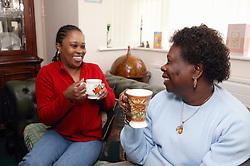 Two women drinking cups of tea,