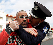 A police officer restrains an anti-Gaddafi protester outside the Libyan Embassy in Attard, outside Valletta, March 21, 2011. Several arrests were made when anti-Gaddafi protesters threw stones at pro-Gaddafi demonstrators and tried to approach the embassy gates, according to local media...REUTERS/Darrin Zammit Lupi (MALTA)