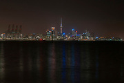 Auckland City, New Zealands largest city, Downtown Skyline by night, with the cranes of Auckland Harbour and the city lights mirroring in the waters of the Hauraki Gulf, as seen from Devonport Fullers ferry building.