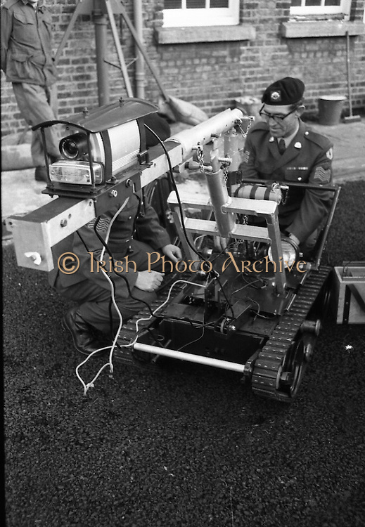 Bomb Disposal Robot.   (J97)..1975..29.12.1975..12.29.1975..29th December 1975..At Clancy Barracks,Dublin the Irish army put on display their newly aquired Bomb Disposal Robot. It would be invaluable in inspecting suspect buildings or vehicles. The series of pictures shows the army demonstration of the equipment..Image shows the final adjustments being made before the vehicle is sent on its way.