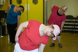 Day Service users with learning disability warming up before a dance class with Care Assistant joining the activity,