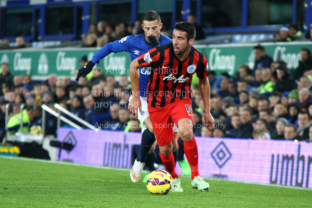 Mauricio Isla of Queens Park Rangers is chased by Kevin Mirallas of Everton. Barclays Premier league match, Everton v Queens Park Rangers at Goodison Park in Liverpool, Merseyside on Monday 15th December 2014.<br /> pic by Chris Stading, Andrew Orchard sports photography.