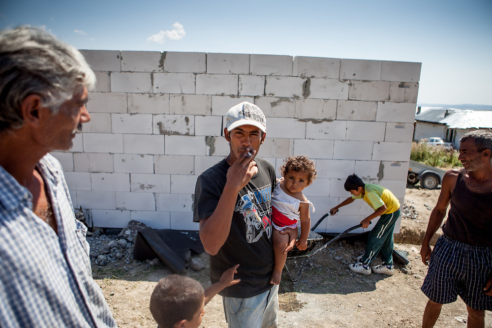 """Grandfather Rudolf (52, left) with his son Rudo who is holding his daughter and others who are among six families which joined a pilot project constructing low-cost houses called """"From Shack into a 3E (Ecological and Energy Efficient) House"""",<br /> which was implemented in the village of Rankovce located about 30 km from Kosice in 2013. The pilot project took place in a marginalized Roma community - all the builders were<br /> unemployed Roma living with their families in difficult conditions."""