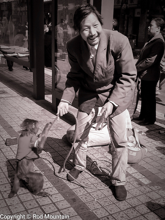 A street performer smiles while handling his monkey in Jianmen City, China.