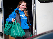 "17 MARCH 2020 - DES MOINES, IOWA: SARAH MERCER-SMITH, with the Boys & Girls Clubs and working with the Des Moines Area Religious Council (DMARC), brings bags of food to a family in the parking lot of Carver Elementary School in Des Moines after giving bags of food to a family. Des Moines Public Schools are closed for at least 30 days because of the Coronavirus outbreak. Des Moines area religious organizations and food banks are working together to bring free food to children in at risk communities. Volunteers and workers are practicing ""social distancing"" by leaving the food packages on the pavement and recipients pick up the packages. Tuesday, the Governor of Iowa ordered all restaurants and bars to close or go to take out only. The Iowa Department of Public Health has urged all public buildings, like libraries and schools, to close, and all schools in Iowa are closed for at least 30 days.     PHOTO BY JACK KURTZ"