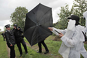 Climate activists from the Building Block, one of three groups of activists, are making their way across fields and pass police to join the ongoing blockade of Coryton oil refinery. The police Forward Intelligence Team has arrived and are photographing activists to identify them later. One way of rying to avoid being identified is using an umbrella to block the view.<br /> <br /> Crude Oil Awakening is a coalition of climate change activist groups. On Saturday Oct 16 they shut the only entrance to Coryton oil refinery in Essex, UK with the aim of highlighting the issues of climate change and the burning of fossil fuels. The blockade meant that a great number of trucks with oil were not able to leave the refinary during the day of action.