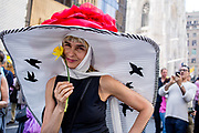 New York, NY - April 16, 2017. A woman coyly holds a daffodil while wearing a hat with a cape-like brim at New York's annual Easter Bonnet Parade and Festival on Fifth Avenue.