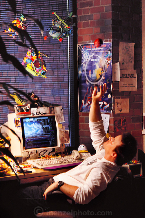 """G. McQueen, senior animator, in his office of Pacific Data Images (PDI) in Sunnyvale, California.  1992. The company does computer animation and digital film effects: morphing. In 1996 PDI began collaborating with DreamWorks SKG, which then acquired PDI in 2004. .Creating believable 3D animated characters (War Games) and seamless transformations known as morphing (""""Black and White"""" and """"She's Mad""""), PDI has been at the forefront of computer imagery. The studio pushed the boundaries of morphing in Michael Jackson's video """"Black or White"""" with a sequence of twelve dynamic transformations of moving characters. In the innovative David Byrne video """"She's Mad,"""" PDI pioneered the technology called performance animation, capturing the motion of David Byrne and infusing an animated character with his distinctive motion. ."""