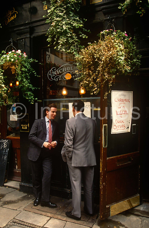 Two young businessmen stand outside a City of London pub with pint glasses on the window ledge, ignoring a warning sign telling drinkers that it's illegal to do so outside, a bylaw of the 1990s era.