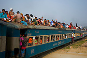 Travelers crowd on top of a train at the main train station in Dhaka, Bangladesh.