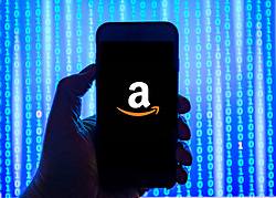 Person holding smart phone with  Amazon.com  logo displayed on the screen. EDITORIAL USE ONLY