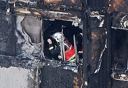 A firefighter investigates a floor after a fire engulfed the 24-storey Grenfell Tower in west London.