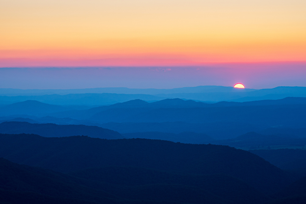 A sliver of the sun can be seen dropping below the distant blue mountain ridges of West Virginia, giving the impression of ocean waves as seen from the top of Peters Mountain at the Hanging Rock Raptor Observatory.
