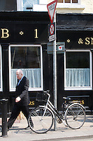 Man walking past bar in Dublin Ireland, bicycle locked to Yield sign