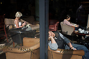 Three woman in the warm sunshine in a window of Caffe Nero in central London. Seated in comfortable chairs bathed in afternoon sunshine, the 3 strangers enjoy the warmth through the window in this central London street near Covent Garden. We see the shadows of the words Panini and Pasta which Nero offer in their UK cafes. One lady checks her phone, another reads a book and the third leans against the glass, fast asleep. Gerry Ford founded Caffè Nero in 1997, now one of the leading UK coffee house operators in the world now with over 600 stores worldwide. They operate in the United Kingdom, Turkey, the Middle East, Poland and Cyprus.