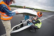 Fietser Rik Houwers wordt in de fiets geholpen. In Soesterberg test het Human Power Team Delft en Amsterdam (HPT) voor het eerst met de nieuwe fiets, de VeloX4. Op de voormalige vliegbasis legt de recordfiets de eerste meters af. In september wil het HPT, dat bestaat uit studenten van de TU Delft en de VU Amsterdam, een poging doen het wereldrecord snelfietsen te verbreken, dat nu op 133,8 km/h staat tijdens de World Human Powered Speed Challenge.<br /> <br /> In Soesterberg the Human Power Team Delft and Amsterdam (HPT) tests their newest bike, the VeloX4. On the track of the former military airport the bike rides its first meters. With the special recumbent bike the HPT, consisting of students of the TU Delft and the VU Amsterdam, also wants to set a new world record cycling in September at the World Human Powered Speed Challenge. The current speed record is 133,8 km/h.
