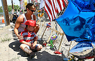 Casen Beyea, 3, wearing a toy fireman's helmet sits next to the cross for Andrew Ashcrast with his mother Christine at a memorial in Prescott, Arizona to firefighters killed in the nearby wildfire July 2, 2013.   An elite squad of 19 Arizona firemen was  killed in the worst U.S. wildland firefighting tragedy in 80 years apparently outflanked and engulfed by wind-whipped flames in seconds, before some could scramble into cocoon-like personal shelters on June 30, 2013. Beyea was a friend at school with Ashcraft. REUTERS/Rick Wilking (UNITED STATES)