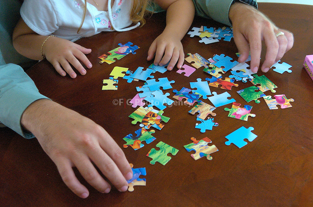 2005/05/31-Caguas, Puerto Rico-A father and his daugther play with a puzzle, as part as a everyday activity for a professional working from home.