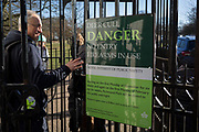 A walker enters Richmond Gate and into Richmond Park where a prominent sign warns that the annual deer cull is taking place in this royal park, on 3rd February 2019, in London, England.