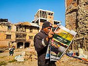 02 MARCH 2017 - SANKHU, NEPAL: A man stands in an empty lot and reads a Nepalese newspaper. A building once stood on the lot, but it was destroyed in the 2015 earthquake. The buildings around the lot, to the right and in the background, were badly damaged but are still standing. There is more construction and rebuilding going on in Sankhu, west of central Kathmandu, than in many other parts of the Kathmandu Valley nearly two years after the earthquake of 25 April 2015 that devastated Nepal. In some villages in the Kathmandu valley workers are working by hand to remove ruble and dig out destroyed buildings. About 9,000 people were killed and another 22,000 injured by the earthquake. The epicenter of the earthquake was east of the Gorka district.   PHOTO BY JACK KURTZ