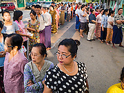 08 NOVEMBER 2015 - YANGON, MYANMAR:  People stand in line to get into their polling place in central Yangon. The citizens of Myanmar went to the polls Sunday to vote in the most democratic elections since 1990. The National League for Democracy, (NLD) the party of Aung San Suu Kyi is widely expected to get the most votes in the election, but it is not certain if they will get enough votes to secure an outright victory. The polls opened at 6AM. In Yangon, some voters started lining up at 4AM and lines were reported to long in many polling stations in Myanmar's largest city.     PHOTO BY JACK KURTZ