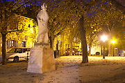 The old stone statue of Cyrano de Bergerac on a square in Bergerac. At night with houses lit up on the town square. on Place de la Myrpe, facing Place du Docteur Cayla Square Bergerac Dordogne France