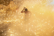 """An attendee walks through sparks flying from a """"little bull"""" firework sculpture during the National Pyrotechnic Festival parade in Tultepec, Mexico state, Mexico. Tultepec, a municipality of about 130,000 people, is famed for small workshops that produce many of the fireworks used on holidays throughout the region."""