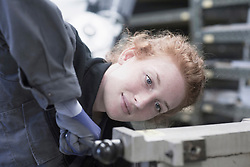Young female engineer operating lever in an industrial plant, Freiburg im Breisgau, Baden-Wuerttemberg, Germany