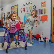 From left, Malia Kearns, 8, Elliot Erlmett, 4, and Hayden Grimmett, 8, race down the hallway during a carnival-style book fair at the George Washington Elementary School in Eleanor, W.V., on Tuesday, July 24, 2018.