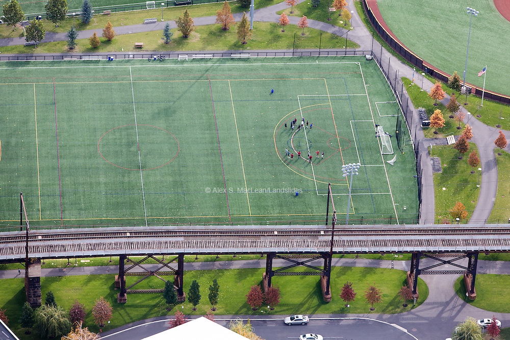 A raised railroad track sits parallel to an athletic field at Penn Park
