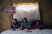 Gilda Manuel Mate with son Vasco Moises and daughter Dercia Moises in her home at her kitchen table. She is HIV positive and a spokesperson in the fight against AIDs and lives in Fidlel Castro Village.