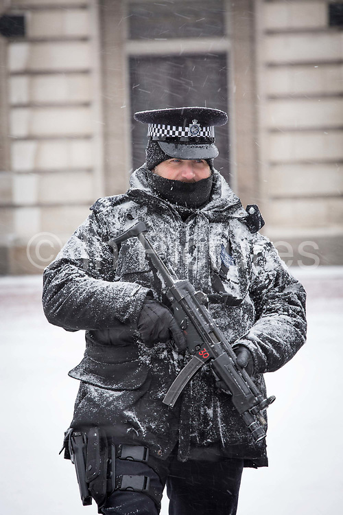 Armed police at Buckingham Palace with a dusting of snow following the arrival of Storm Emma which is set to bring further widespread disruption to many parts of the UK on 2nd March 2018 in Central London, London, United Kingdom. Freezing weather conditions dubbed the Beast from the East brings snow and sub-zero temperatures to the UK.