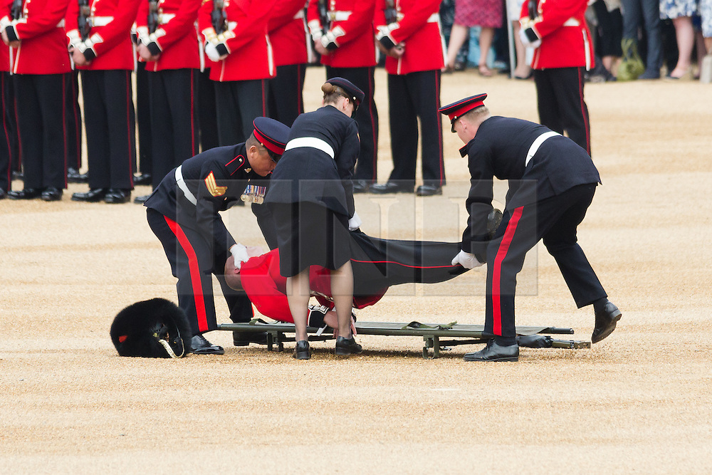 © Licensed to London News Pictures. 11/06/2016. LONDON, UK.  A guardsman collapses during the Trooping the Colour ceremony in Horse Guards parade. Around 1,500 soldiers take part in the annual Trooping of the Colour ceremony, which this year celebrates the 90th birthday of Her Majesty Queen Elizabeth II.  Photo credit: Vickie Flores/LNP