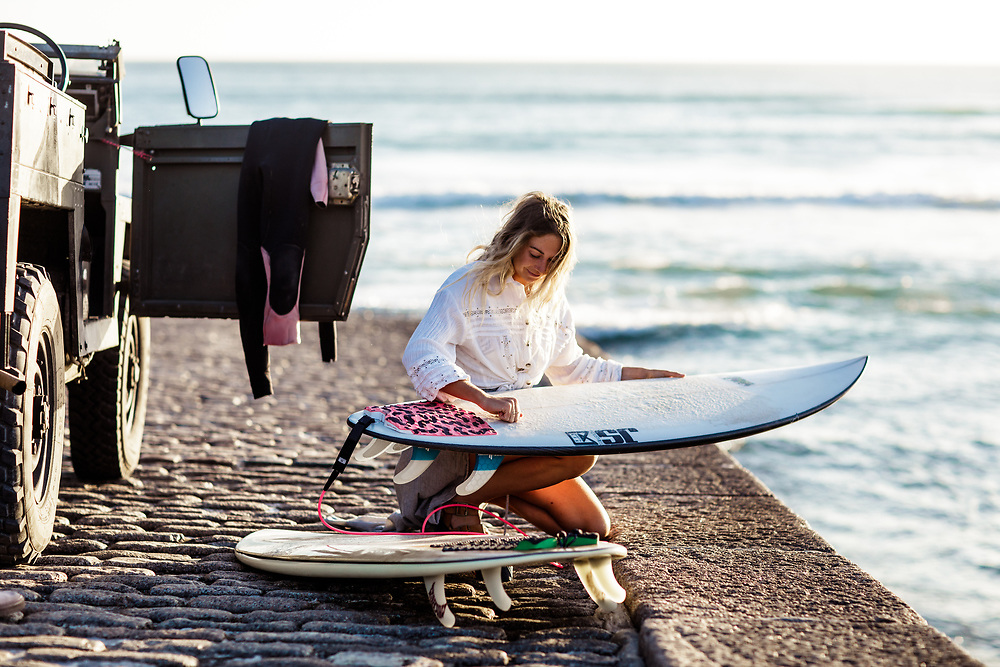 Woman waxing her surfboard getting ready to go surfing, with her landrover parked on the slipway at St Ouen's Bay, Jersey, CI