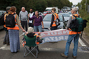 A motorist contests Insulate Britain climate activists blocking two slip roads from the M25, causing long tailbacks on the motorway, as part of a new campaign intended to push the UK government to make significant legislative change to start lowering emissions on 13th September 2021 in Godstone, United Kingdom. The activists, who wrote to Prime Minister Boris Johnson on 13th August, are demanding that the government immediately promises both to fully fund and ensure the insulation of all social housing in Britain by 2025 and to produce within four months a legally binding national plan to fully fund and ensure the full low-energy and low-carbon whole-house retrofit, with no externalised costs, of all homes in Britain by 2030 as part of a just transition to full decarbonisation of all parts of society and the economy.