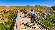 Cyclists crossing a tressel bridge on the Otago Central Rail Trail, Otago, South Island, New Zealand