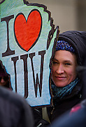 """MADISON, WI — FEBRUARY 13, 2015: A rallygoer holds a sign in support of the University of Wisconsin during the """"Stop the Cuts"""" Rally on Library Mall, Saturday, February 14, 2015. The rally drew hundreds of student, faculty and community supporters in spite of the cold Midwest weather."""