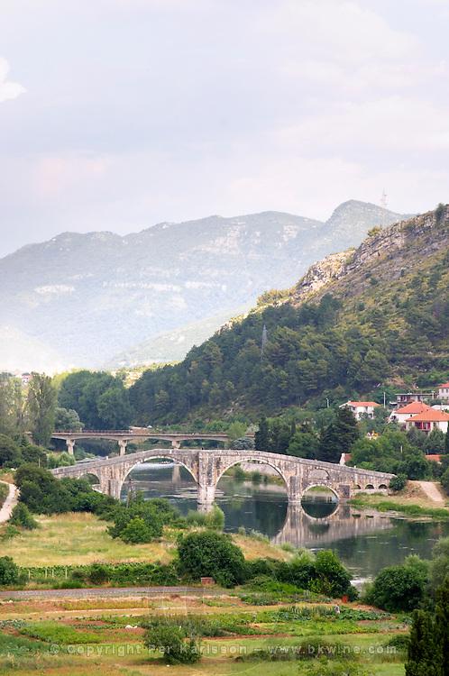 An old Roman stone bridge across the river Trebisnjica. Houses. against a mountain backdrop. Trebinje. Republika Srpska. Bosnia Herzegovina, Europe.