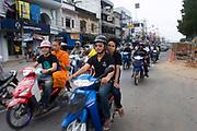 Motos and bikes pass in a procession through Krabi Town