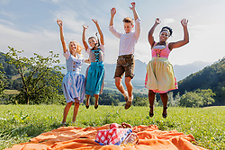 Teenage friends jumping for joy during picnic, Bavaria, Germany