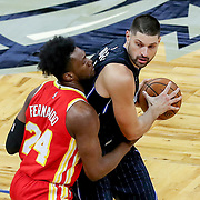 ORLANDO, FL - MARCH 03: Bruno Fernando #24 of the Atlanta Hawks defends against Nikola Vucevic #9 of the Orlando Magic during the first half at Amway Center on March 3, 2021 in Orlando, Florida. NOTE TO USER: User expressly acknowledges and agrees that, by downloading and or using this photograph, User is consenting to the terms and conditions of the Getty Images License Agreement. (Photo by Alex Menendez/Getty Images)*** Local Caption *** Bruno Fernando; Nikola Vucevic