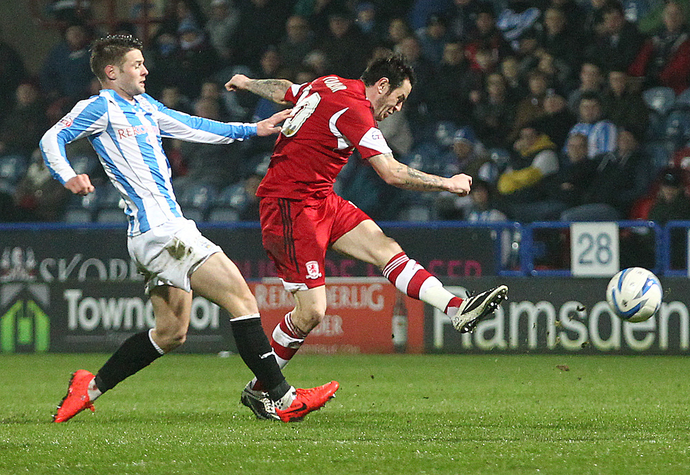 Middlesbrough's Lee Tomlin unleashes a shot on goal during the second half despite the attentions of Huddersfield Town's Oliver Norwood<br /> <br /> Photo by Rich Linley/CameraSport<br /> <br /> Football - The Football League Sky Bet Championship - Huddersfield Town v Middlesbrough - Tuesday 25th March 2014 - The John Smith's Stadium - Huddersfield<br /> <br /> © CameraSport - 43 Linden Ave. Countesthorpe. Leicester. England. LE8 5PG - Tel: +44 (0) 116 277 4147 - admin@camerasport.com - www.camerasport.com