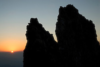 The morning sun peeks over the horizon past the East Horn near the top of Drizzlepus on the southeast sloap of Mount Moran.