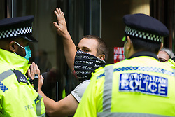 An activist from HS2 Rebellion, an umbrella campaign group comprising longstanding campaigners against the HS2 high-speed rail link as well as Extinction Rebellion activists, is pictured glued to the doors of the Department for Transport during a protest on 4 September 2020 in London, United Kingdom. Activists glued themselves to the doors and pavement outside the building and sprayed fake blood around the entrance during a protest which coincided with an announcement by HS2 Ltd that construction of the controversial £106bn high-speed rail link will now commence.