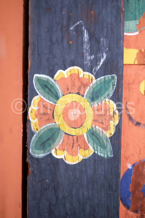 A typical Bhutanese hand painted decoration on a farmhouse wall in Gorgona village, Bhutan. Lhazo (painting) is one of the 'Zong Chusum' or 13 traditional arts and crafts of Bhutan. Lhazo (painting) includes painting of religious pictures, murals and frescoes in temples and dzongs as well as the colourful images on the exterior walls of Bhutanese houses.