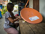 14 OCTOBER 2015 - BANGKOK, THAILAND:  DAOLAOM SITTHIRUNG, 47,  takes down her satellite dish while packing up her home in the Wat Kalayanamit neighborhood. Fifty-four homes around Wat Kalayanamit, a historic Buddhist temple on the Chao Phraya River in the Thonburi section of Bangkok, are being razed and the residents evicted to make way for new development at the temple. The abbot of the temple said he was evicting the residents, who have lived on the temple grounds for generations, because their homes are unsafe and because he wants to improve the temple grounds. The evictions are a part of a Bangkok trend, especially along the Chao Phraya River and BTS light rail lines. Low income people are being evicted from their long time homes to make way for urban renewal.         PHOTO BY JACK KURTZ