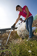 Cleaning up the Dominguez Channel at Artesia Transit Center. Over 14,000 volunteers took part in Coastal Cleanup Day in Los Angeles County, cleaning up beaches, parks, alleys, creeks, highways and storm drains at 69 different sites. Over 300,000 pounds of debris and recyclables were removed by the various environmental organizations, community groups, families, local businesses, faith-based organizations and students that took part. Los Angeles, California, USA